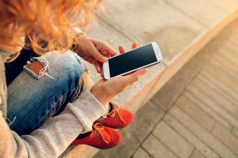 Девушка с рыжими волосами сидит на улице с мобильным в руках
